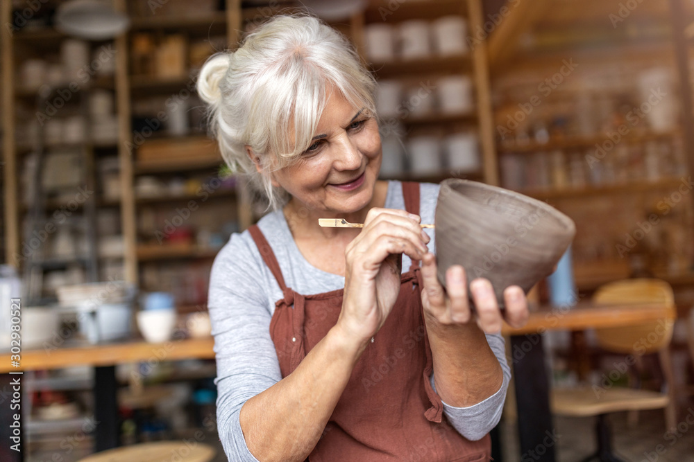 Fototapeta Senior woman pottery artist makes ceramics from clay