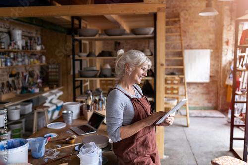 Obraz Senior craftswoman with tablet computer in art studio  - fototapety do salonu