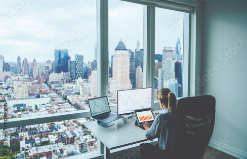 Fototapeta Rear view female employee working on PC computers with financial information on screen sitting at office table with downtown skyscrapers view behind window. Successful businesswoman at her workspace obraz