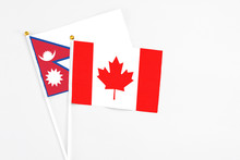 Canada And Nepal Stick Flags On White Background. High Quality Fabric, Miniature National Flag. Peaceful Global Concept.White Floor For Copy Space.