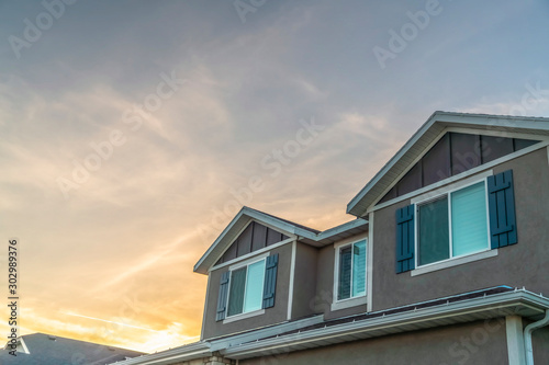 Photo Exterior upper storey of a home with golden cloudy sky background at sunset