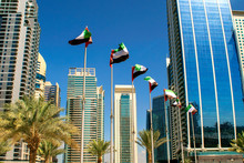 View Of Dubai Buildings With UAE Flags. United Arab Emirates Flags Waving On Blue Sky Background. Independence Day. UAE Flags On Street. Flag Day
