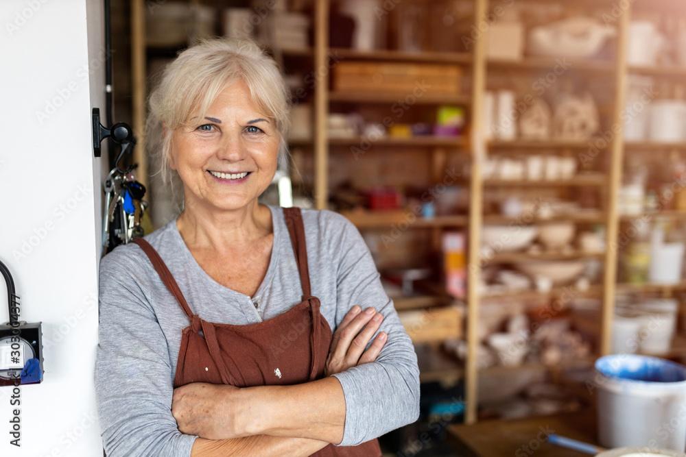 Fototapeta Portrait of senior female pottery artist in her art studio