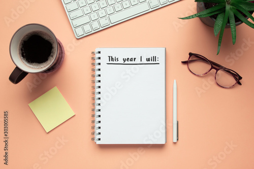 Stock photo of 2020 new year notebook with list of resolutions and objects on pink background