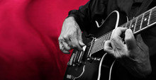 Guitarist Hands And Guitar Black And White On A Red Background Close Up. Playing Electric Guitar. Copy Spaces.