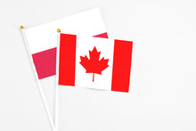 Canada And Poland Stick Flags On White Background. High Quality Fabric, Miniature National Flag. Peaceful Global Concept.White Floor For Copy Space.