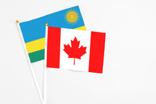 Canada And Rwanda Stick Flags On White Background. High Quality Fabric, Miniature National Flag. Peaceful Global Concept.White Floor For Copy Space.