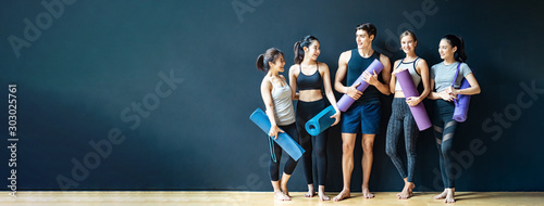 Fototapeta Group of diversity ethnic people holding Yoga mat talking together with smile. Asian girl laughing with funny face after finish training class. Happy and relax time in group of friend in Banner size. obraz