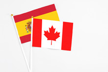 Canada And Spain Stick Flags On White Background. High Quality Fabric, Miniature National Flag. Peaceful Global Concept.White Floor For Copy Space.