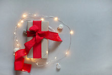 Gift Box With Red Ribbon, Curled Garland With Lights. Blank For Postcard, Poster, Place For Your Text, Shallow Depth Of Field
