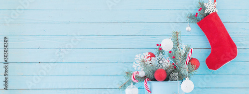 Christmas stocking and fir branches in blue buchet on blue wooden background Tableau sur Toile