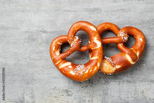 Fotografiet Freshly baked bavarian pretzel with salt on rustic table.