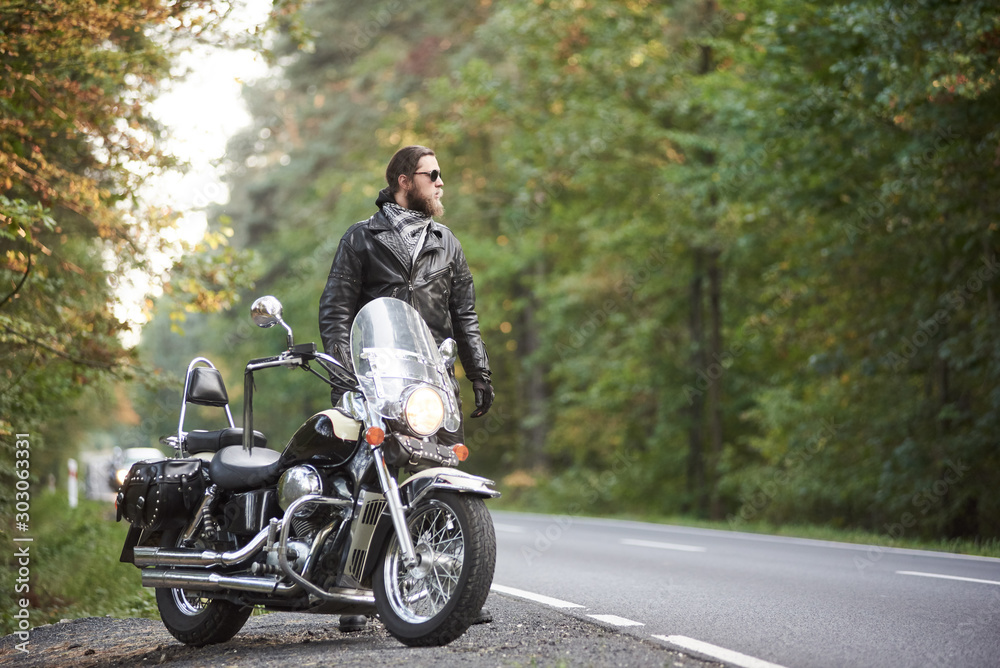 Fototapeta Young bearded tall athletic motorcyclist in dark sunglasses, black leather jacket and gloves standing at shiny modern powerful motorbike on blurred background of hilly asphalt road and green trees.