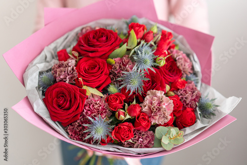 Mixed bouquet of red tones. Beautiful bunch of fresh flowers in womans hands. The work of the florist at a flower shop. Fresh cut flower. © malkovkosta
