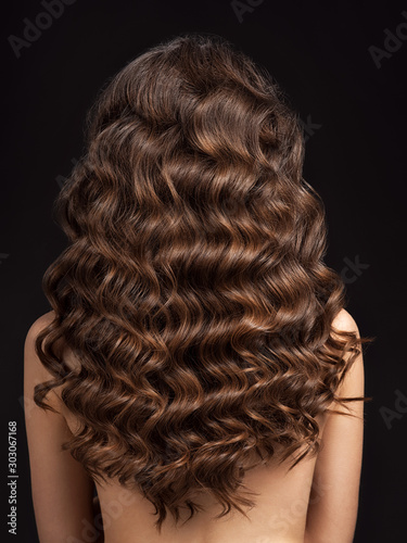 Fototapeta Girl with long, curly hair, rear view. Hair texture, close-up.