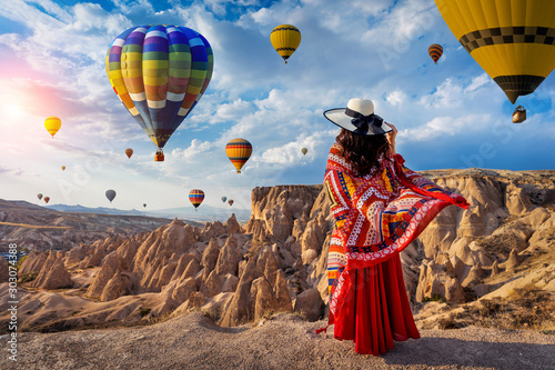 Fototapeta Beautiful girl standing and looking to hot air balloons in Cappadocia, Turkey