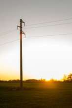 A Line Of Electric Poles With Cables Of Electricity In A Field With A Forest In Background In Autumn During Sunset.