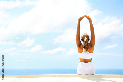 Beautiful woman making stretching exercises in the beach Wallpaper Mural