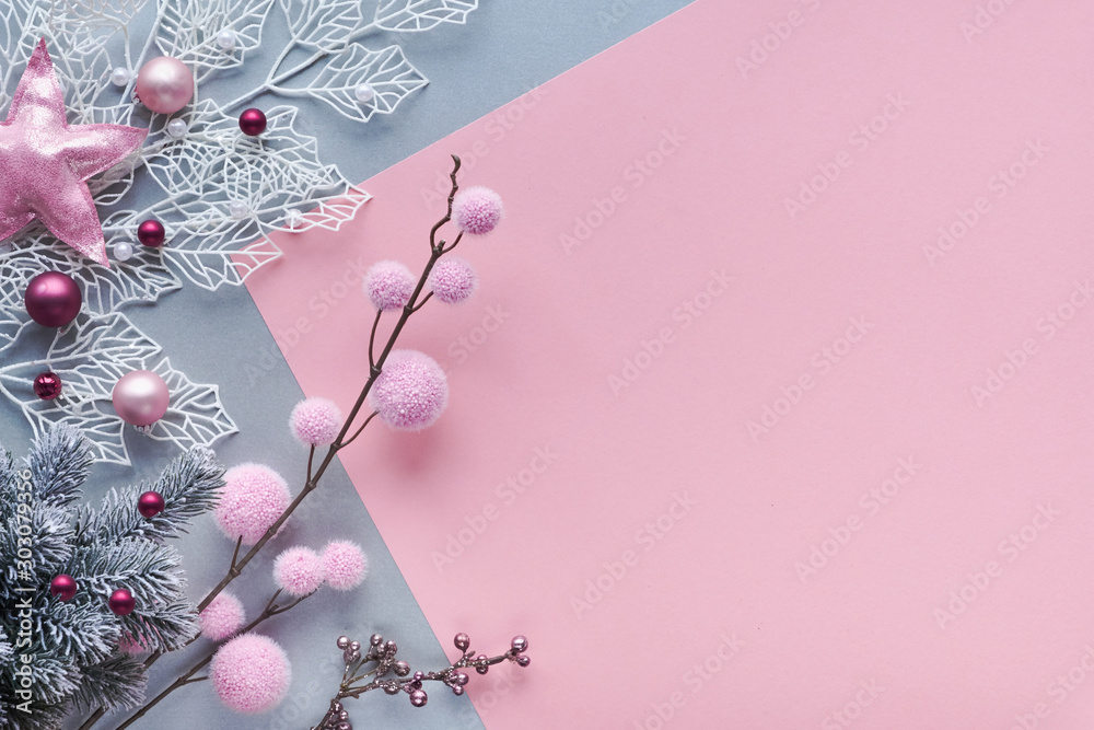 Fototapeta Christmas flat lay in two color paper background, pink and silver, and copy-space. Decorative white winter twigs with shiny geometric leaves and soft textile baubles and scattered glass Xmas balls.