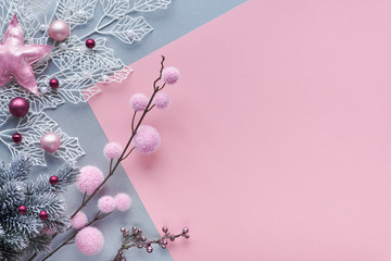 Christmas flat lay in two color paper background, pink and silver, and copy-space. Decorative white winter twigs with shiny geometric leaves and soft textile baubles and scattered glass Xmas balls.