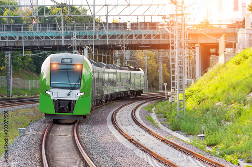 Fotografía  Passenger electric train rides on the turn of the railway line under the automobile bridge