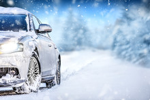 Luxury Car On Winter Road, Blur Mountains Background. Tires In Snow Highway.