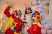Clowns From The Circus On The Girls Birthday. Birthday Girl Blows Out A Cake. Party For Children.
