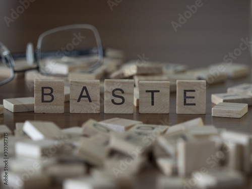 Photo Baste the word or concept represented by wooden letter tiles