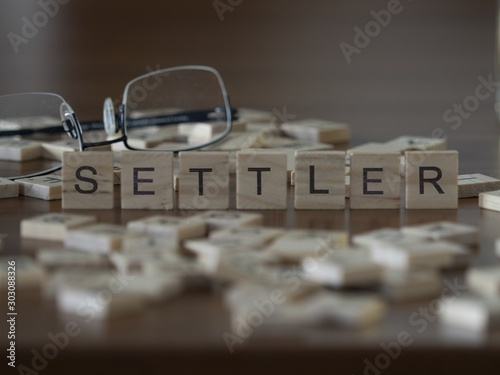 Fotomural  Settler the word or concept represented by wooden letter tiles