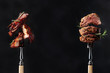 Grilled pork belly and beef steak with rosemary on a black background.