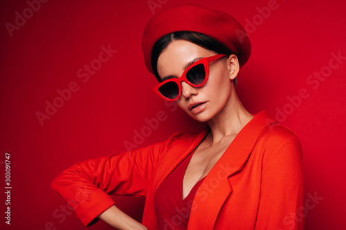 Portrait side view of young attractive model in red outfit posing on camera alone Canvas Print