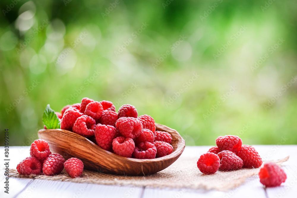 Fototapeta Ripe fresh raspberry in wooden rustic bowl on table. - obraz na płótnie