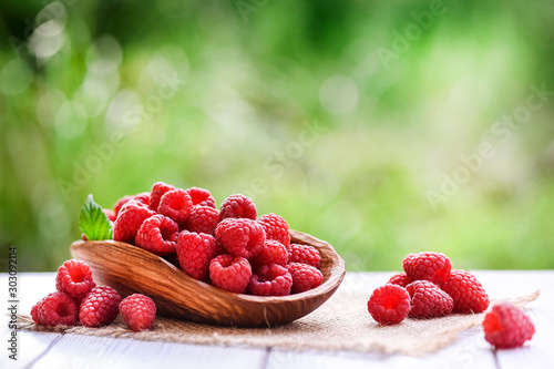 Fotografía Ripe fresh raspberry in wooden rustic bowl on table.