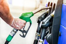 Man After Refueling Gasoline At Gas Station. Hand With Clear Gloves Put Fuel Pump Or Pistol Into The Stand.