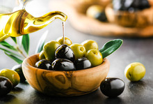 Pouring Fresh Virgin Olive Oil On Green And Black Ripe Olives In Bowl, On Dark Stone Table Or Black Background.
