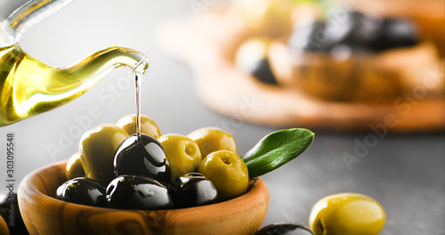 Fototapeta Pour olive oil on ripe green and black olives in wooden bowl. Banner or panorama. obraz