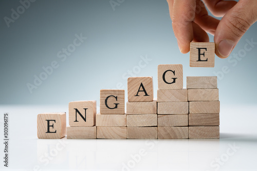 Fototapeta Person Arranging Wooden Blocks Showing Engage Text