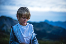 At Dusk, Portrait Of A 7 Years Old Kid Looking Down, Mountain Landscape In The Background