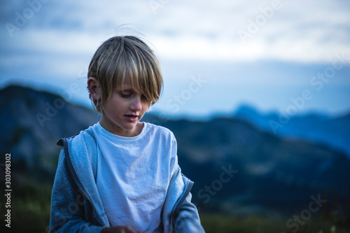 Obraz At dusk, portrait of a 7 years old kid looking down, mountain landscape in the background - fototapety do salonu