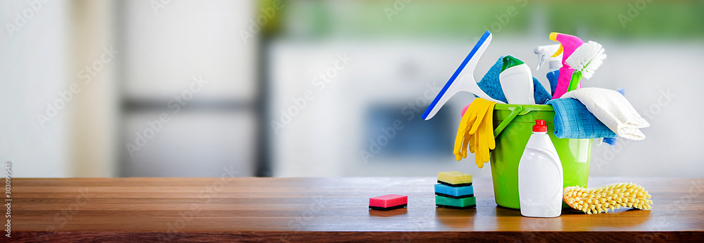 Fototapeta Bucket with cleaning items on wooden table and blurry modern kitchen background. Washing set colorful with copy space banner.