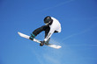 canvas print picture - Skier Snowboarder jumping through air with sky in background