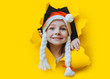 Waiting for a Christmas gift. A beautiful little smiling girl in a red Santa hat with pigtail looks out of a hole in yellow pastel paper. Christmas and New Year concept. Copy space. Torn background.