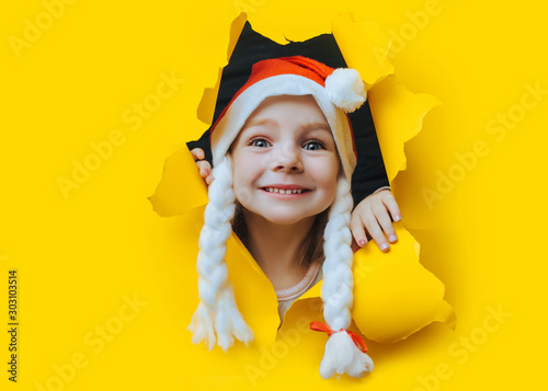 Obraz Waiting for a Christmas gift. A beautiful little smiling girl in a red Santa hat with pigtail looks out of a hole in yellow pastel paper. Christmas and New Year concept. Copy space. Torn background. - fototapety do salonu