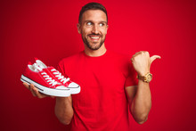 Young Man Holding Casual Sneakers Shoes Over Red Isolated Background Pointing And Showing With Thumb Up To The Side With Happy Face Smiling