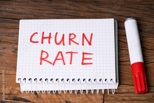 Fotomural Churn Rate Text On Checkered Notepad With Marker Over Table