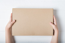 Rectangular Cardboard Box In Children's Hands. Top View, White Background
