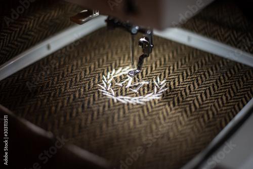 Photo Embroidery design alphabet monogram M on brown fabrics embroider by machine