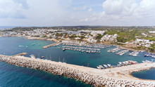 Aerial View Of The Southernmost Point In Salento , Town Of Santa Maria Di Leuca, With Boats And In Yachts In Busy Port Sheltered By Stone Barrier .