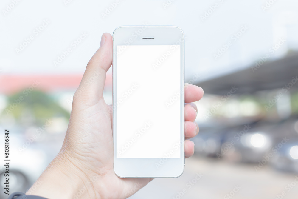 Fototapeta Close-up of a young woman using a cell phone on a blank white screen in the middle of a mall, Space for text