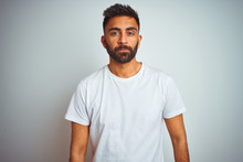 Young Indian Man Wearing T-shirt Standing Over Isolated White Background Relaxed With Serious Expression On Face. Simple And Natural Looking At The Camera.